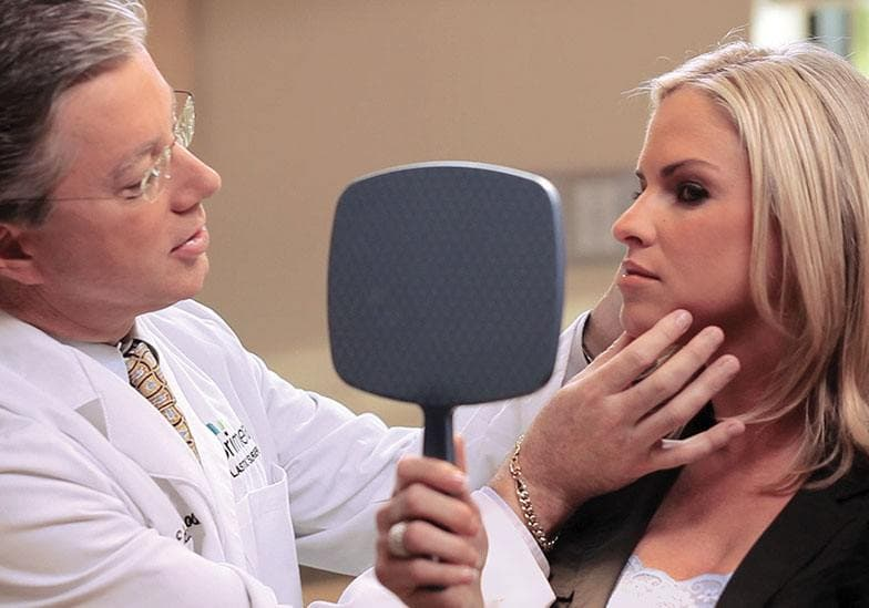 Dr. Gross consulting with a female patient looking in the mirror