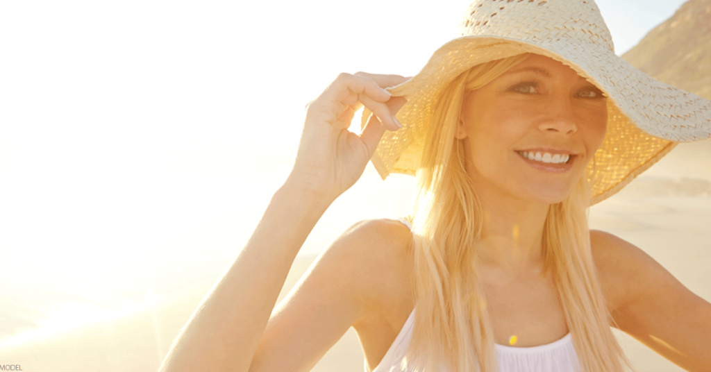 Woman on the beach wearing a sun hat smiling at camera